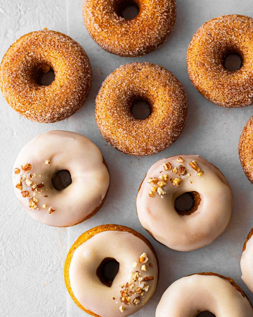 Flatlay of vegan pumpkin spice donuts, half with a white maple glaze and pecans, and half with a spiced granulated sugar coating.