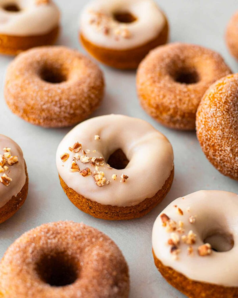 Close up of one glazed pumpkin donut amongst other donuts.