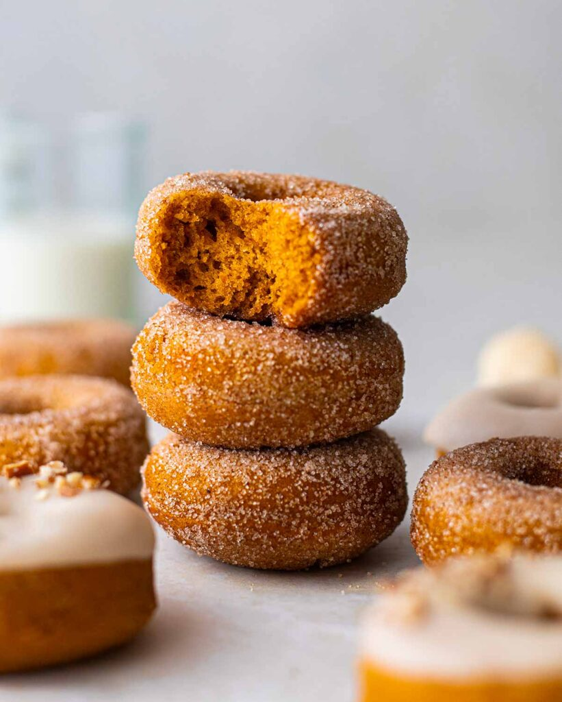 Stack of sugar coated and thick donuts showing golden orange and fluffy interior.